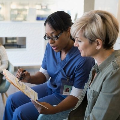 Female patient reviewing chart with female nurse